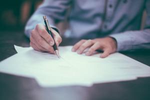 man signing on document